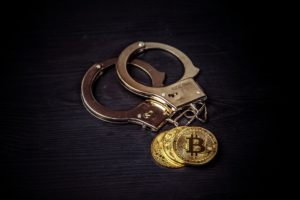 Bitcoins and handcuffs to illustrate if bitcoin is legal in Nigeria