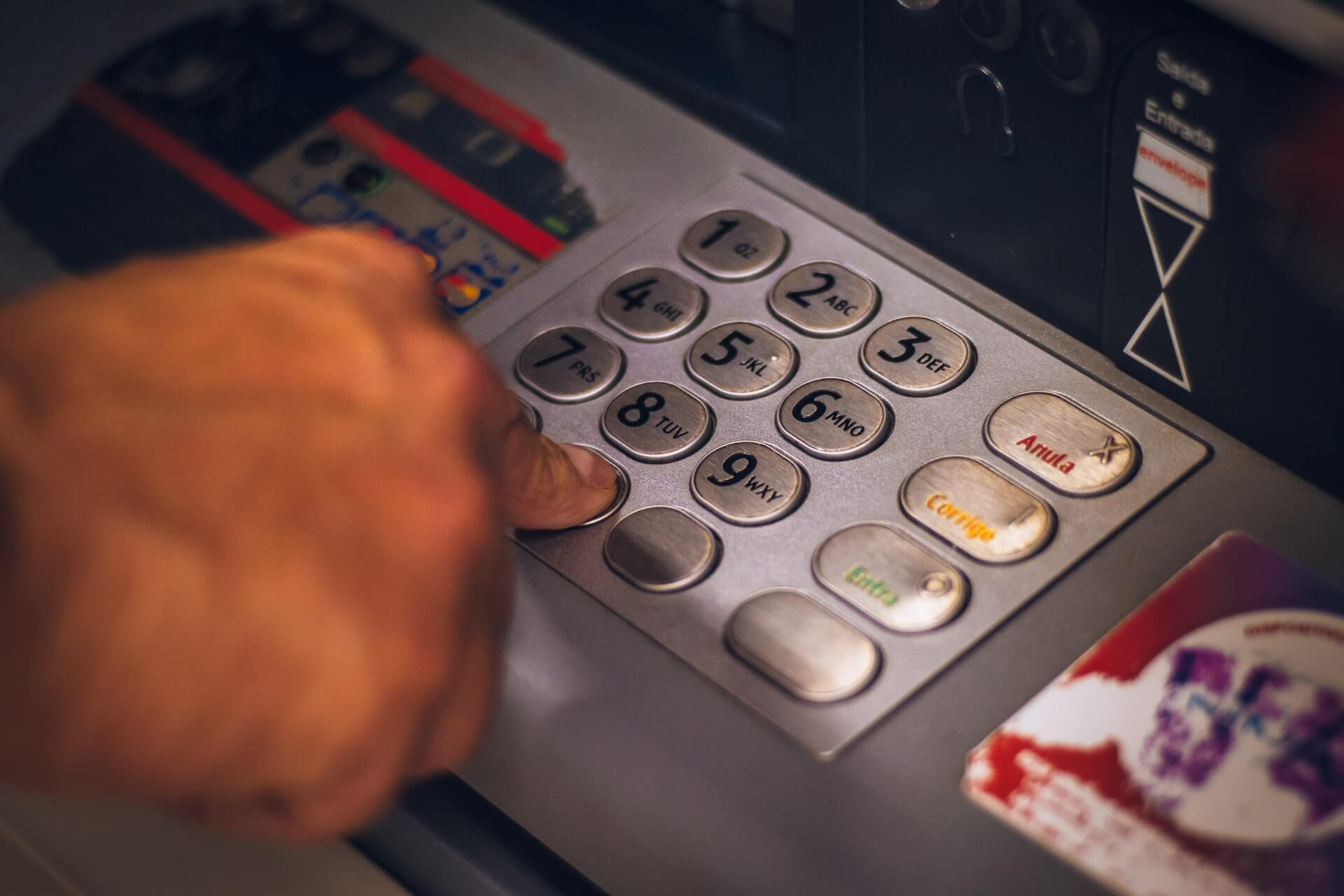 Close up photo of person inputting pin at an atm machine