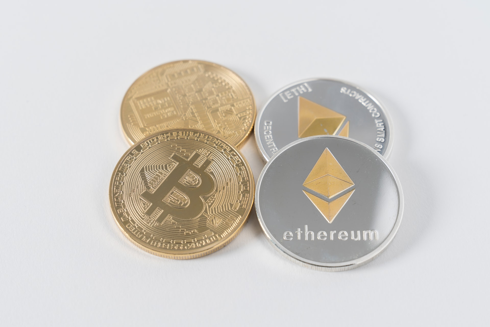 Image of two bitcoins next to two ethereum coins to illustrate the idea of what is ethereum and its differences to bitcoin.